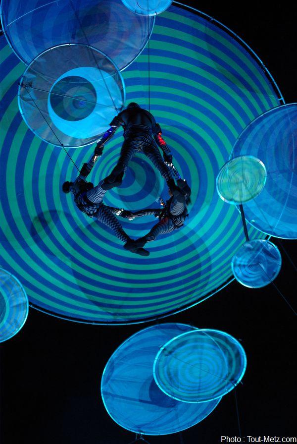 Les artistes de la compagnie espagnole Voalá Project, une quinzaine environ, sont suspendus à 30 mètres du sol. Leur spectacle offre des effets visuels psychédéliques inspirés du courant Optical Art des années 60.