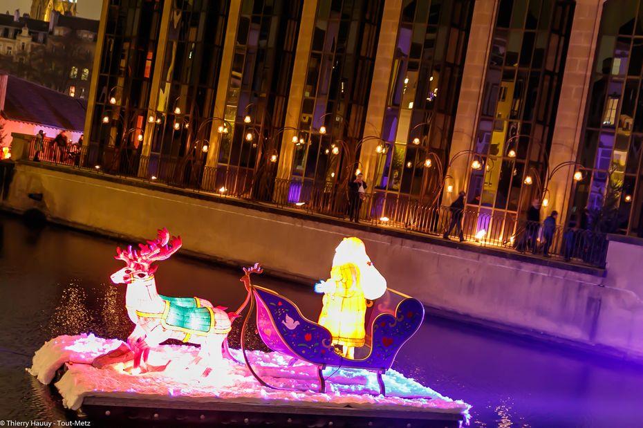 Vue de l'autre côté, on aperçoit au second plan l'allée aux lanternes de Meisenthal. Au premier plan, un Père Noël posé sur l'eau avec son traîneau prêt à décoller pour sa longue nuit de travail le 24 décembre au soir.