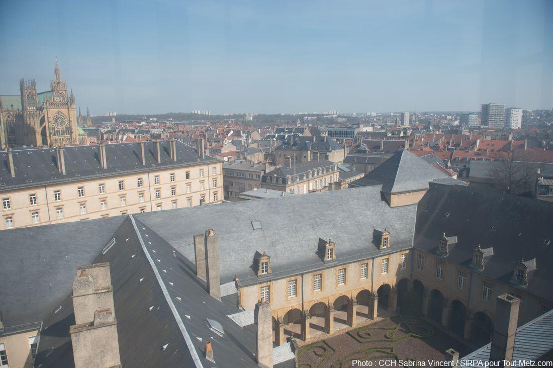 """A l'opposé de la vue précédente, le centre ville s'étend. Au 1er plan le cloître de l'abbaye St Arnoul, la tour carrée imbriquée dans le toit est l'ancienne entrée du bâtiment. En haut à gauche on reconnaît la Cathédrale de Metz. Juste en dessous, la résidence des officiers : des chambres pour les officiers loin de leurs familles. Ce bâtiment, appelé """"celibatorium"""" fut construit pour empêcher les élèves de l'école militaire d'aller s'encanailler avec les filles de la ville. Photo : Sabrina Vincent (SIRPA), avril 2015"""