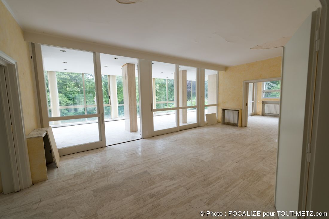 Nous voici à l'intérieur de la maison du colonel, au rez-de-chaussée. L'espace est un salon de grand volume avec cheminée, donnant sur une sorte de salle plutôt à vocation réceptive derrière l'immense baie vitrée.